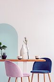 White vase on wooden table with fancy dining room interior with white and blue wall