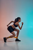 I love fitness. Full length of young athlete woman in sports clothing exercising with a resistance band while standing in studio against colorful background