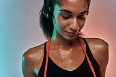 After workout. Portrait of young sporty woman in headphones with jumping rope on her shoulders keeping eyes closed and listening music