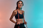 Music is my motivation. Sporty young woman in headphones holding jumping rope on shoulders and looking at camera with smile while standing against colorful background