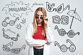 Fashion girl. Close up portrait of attractive asian woman adjusting her sunglasses and looking at camera while standing against grey background with hand drawn doodles on it.