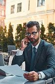 I am working everywhere. Portrait of handsome bearded businessman in eyeglasses talking by phone with client and looking at documents while sitting in restaurant outdoors