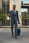 Always in touch. Full length of young and handsome bearded man in suit pulling his luggage and looking at his smartphone while walking outdoors