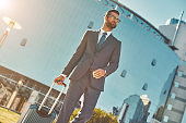 Business trip. Young and handsome bearded man in full suit pulling his luggage and looking away while walking outdoors