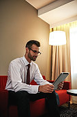 Spectacled business man with suitcase and tablet sitting on sofa at hotel hall