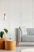 Wooden stools and gray sofa in modern interior