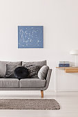 Blue abstract painting on white wall of fashionable living room interior with grey couch and console table
