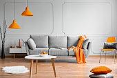 Orange lamp above grey scandinavian sofa in modern interior