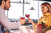 Solemn moments. Couple holding red wine in glasses in restaurant