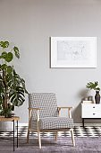 Elegant vintage armchair in grey living room interior with painting on the wall