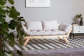 Silver abstract painting on grey wall above scandinavian futon