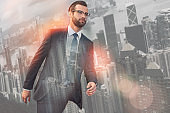 Pure confidence. Portrait of young bearded businessman in suit and glasses walking outdoors against of morning cityscape background.