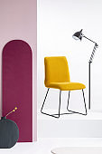 Stylish velvet yellow chair next to tall industrial black lamp in white interior