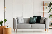 Designed gray couch with wooden legs in modern interior