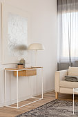 White industrial lamp, photo in frame and plant in pot on wooden console table in elegant living room with white wall