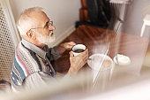 Lonely senior man sitting at kitchen table drinking tea