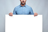 Your text here. Cropped photo of handsome bearded man in casual clothes holding empty blank board while standing against grey background