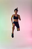 Do it! Full length of young athlete woman with perfect body in sports clothing jumping in studio against colorful background
