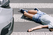Teenage schoolkid lying on the street after terrible car crash on pedestrian crossing