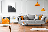 Orange lamps above grey couch in living room interior with posters and silver table. Real photo