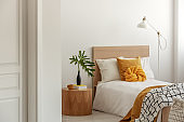 Yellow pillows and blanket on white single wooden bed