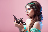 Oriental fairy tale, a young Princess woman with a magic lamp in her hands.