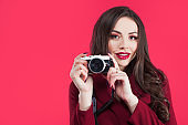 Trendy blogger use the camera on pink background. Young woman with camera