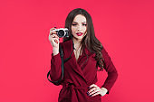 Trendy blogger on pink background. Young woman with camera