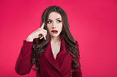 Crazy girl on pink background. Young beautiful woman with bright makeup. The brunette grabbed her head.