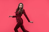 Stylish glamorous girl. Attractive young brunette dressed in fuchsia color, fuchsia color background