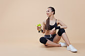 Athletic brunette girl, in sports uniform, sits, rests after a workout, with a bottle in her hand, drinking water.