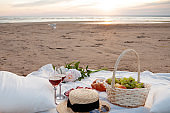 Picnic in the rays of the setting sun on the sand. On the plaid lies fruit basket, glasses, flowers and sweet pastries.