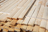 Pile of raw wood planks. Building process, construction site, carpentry, dry building industry concept.