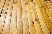 Pile of prepared stained wood planks. Building process, construction site, carpentry, dry building industry concept.