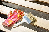 Protecting gloves and paintbrush on wooden surface. Carpentry, wood treatment, hard at work, home improvement, do-it-yourself concept.