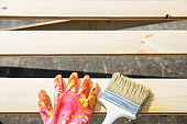 Protecting gloves and paintbrush on wooden planks. Carpentry, wood treatment, hard at work, home improvement, do-it-yourself concept.