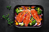 Salmon. Cooking fresh raw salmon fish steaks with vegetables, broccoli, carrot and onion on black background, top view