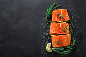 Salmon. Fresh raw salmon fish fillet with cooking ingredients, herbs and lemon on black background, top view