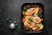 Salmon. Baked salmon fish steaks with vegetables, broccoli, carrot and onion on black background, top view