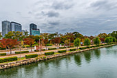 cityscape of autumn scene of Osaka city with park, modern buildings and river, Japan