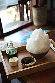 Delicious Japanese sweet shaved ice green tea on wooden table in japanese cafe