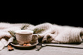 Hot coffee cup wrapped up in a cozy blanket on a wooden table with winter decorations