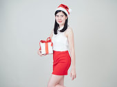 Woman wearing christmas hat and holding gift box isolated on white background