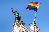 A young woman waves a rainbow flag high during the Gay Pride parade in Paris, France.