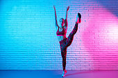 Pretty young slim gymnast woman in sports clothing stretching in front of brick wall in neon lights. Flexible muscular woman doing gymnastic split.