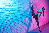Attractive young slim gymnast woman in sports clothing stretching on brick wall in neon lights. Flexible muscular woman doing gymnastic split.