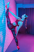 Young slim gymnast woman in sports clothing stretching on brick wall in neon lights. Flexible muscular woman doing gymnastic split.