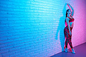 Cheerful young slim gymnast woman in sports clothing posing on brick wall in neon lights. Flexible muscular woman doing gymnastic split.