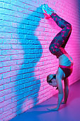 Attractive young slim gymnast woman in sports clothing stretching on brick wall in neon lights. Flexible muscular woman doing gymnastic exercises.