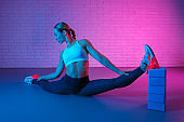Handsome young slim gymnast woman in sports clothing stretching against brick wall in neon lights. Flexible muscular woman doing advanced gymnastic split.